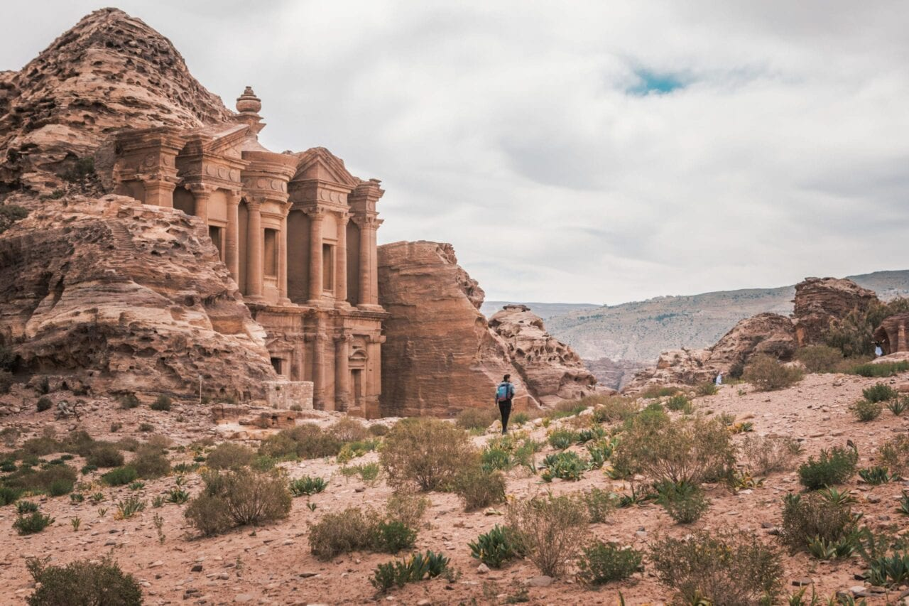 A hiker stands in front of Al Der Petra in a desert landscape.