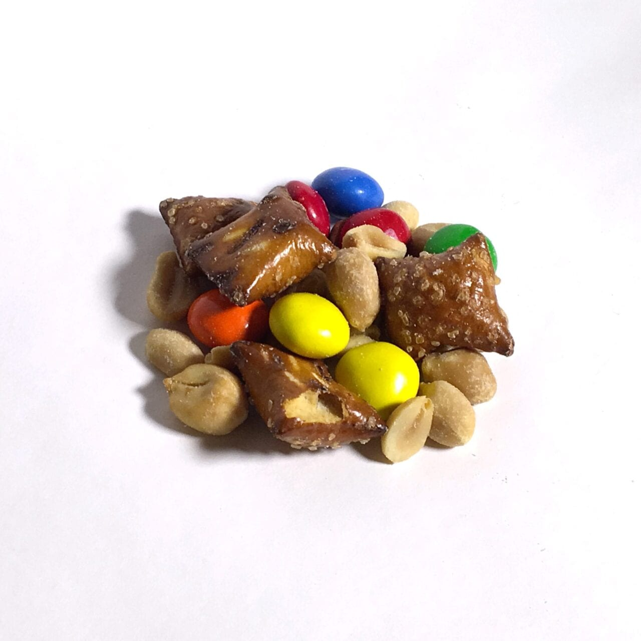 A pile of GORP trail mix including nuts and m&ms.