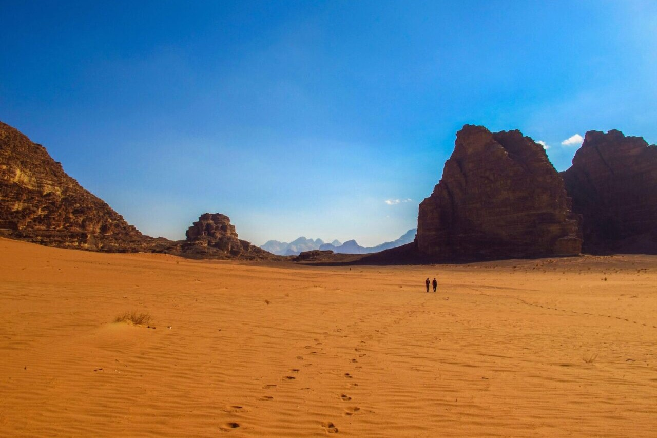 Two hikers walk through a red sandy desert towards distant rock formations.