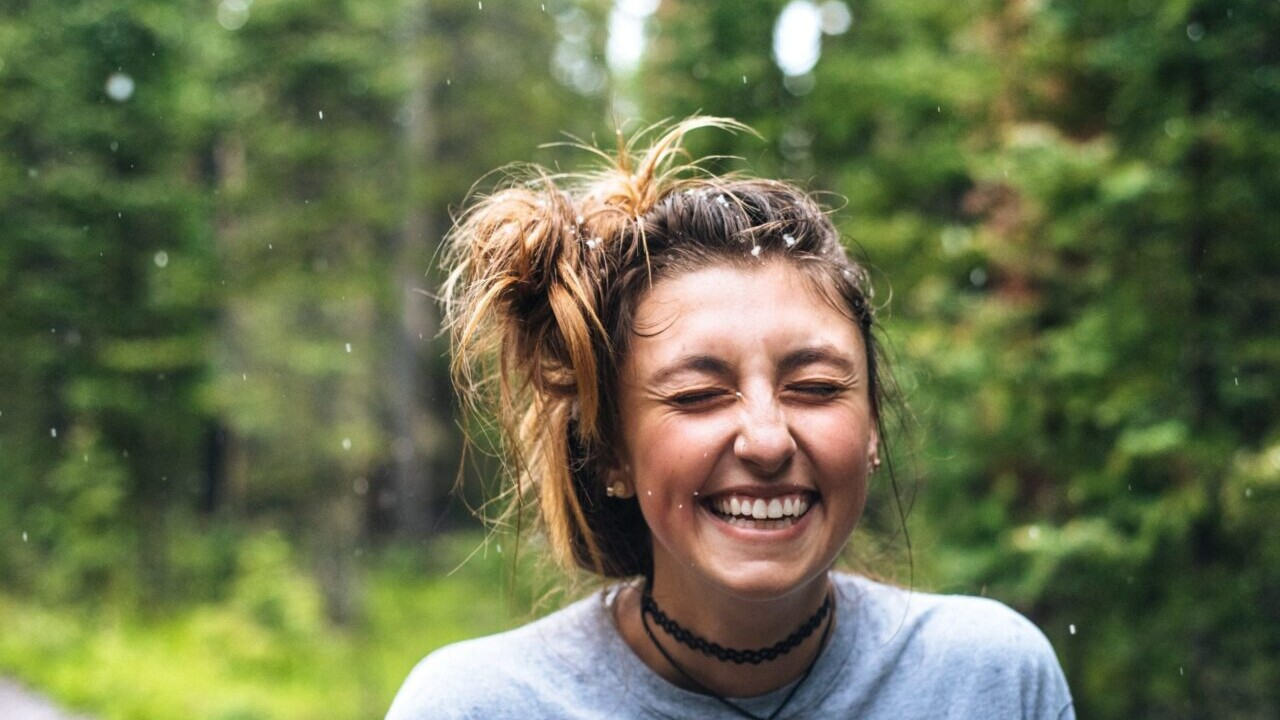 A girl with borwn hair smiles in the rainy green forest.