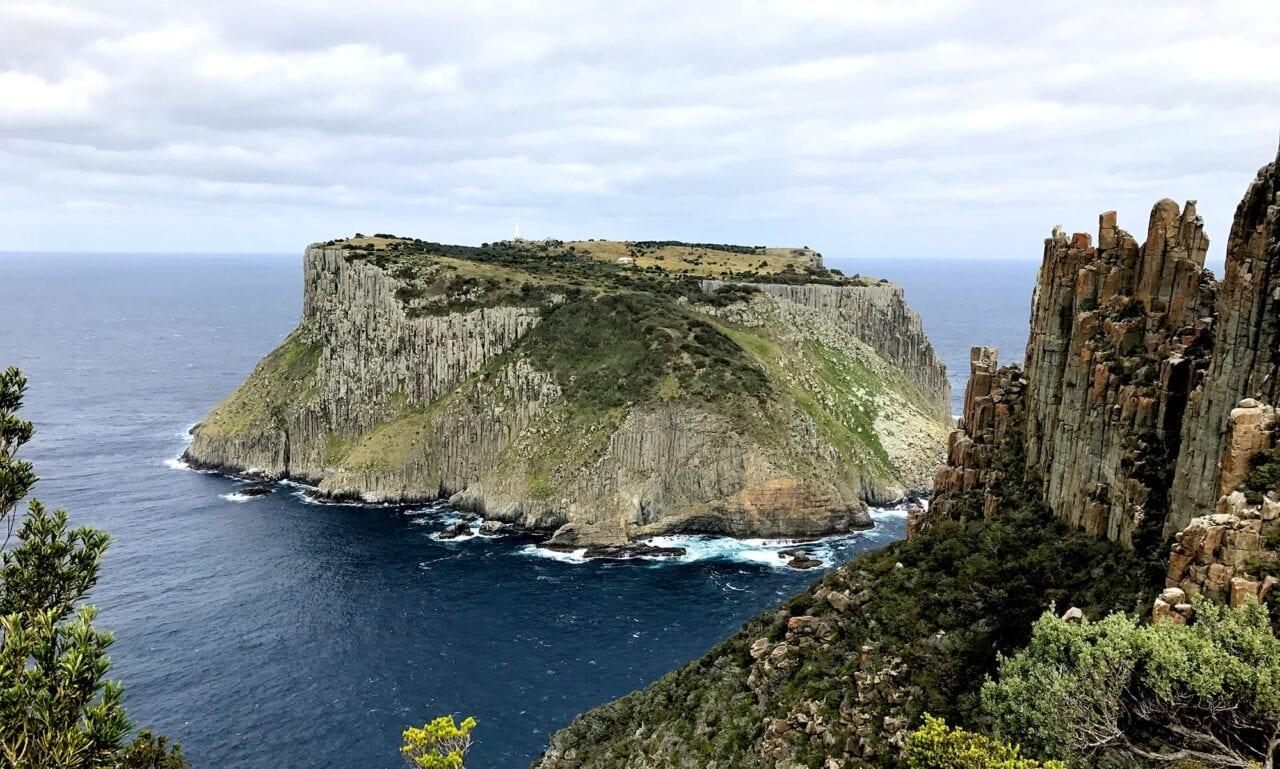 A rocky island sits in the blue ocean along a rocky coastline.