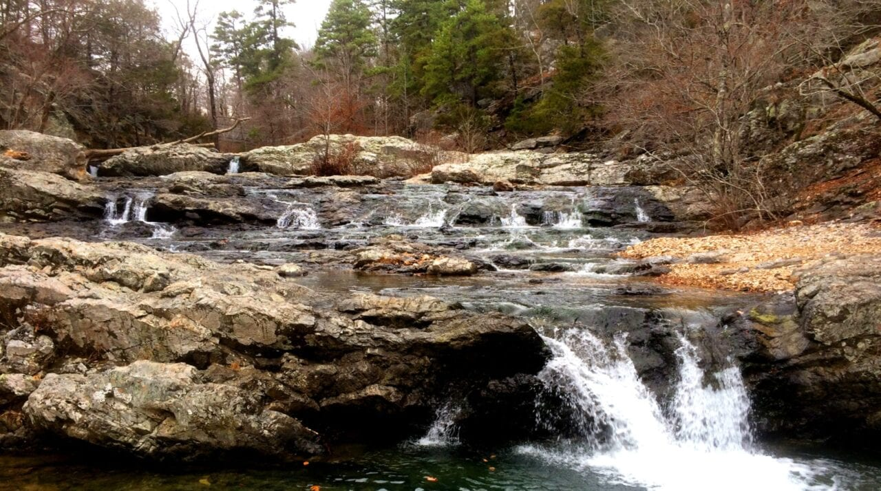 A waterfall cascades over rocks in a stream in a deciduous forest.
