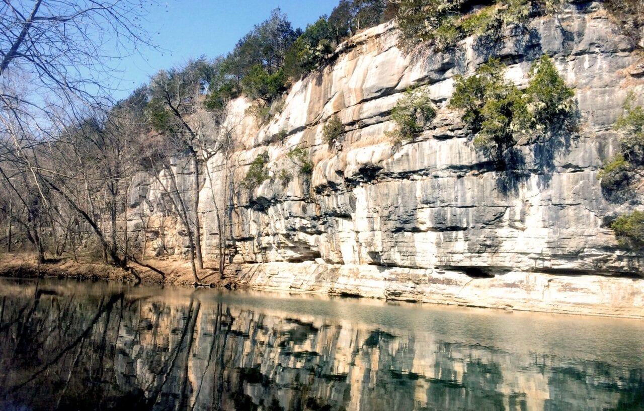 A glassy calm river flows by a tall rock wall under blue skies.
