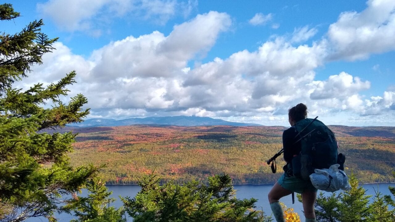 A hiker standing on a mountain looking out at a beautiful landscape.