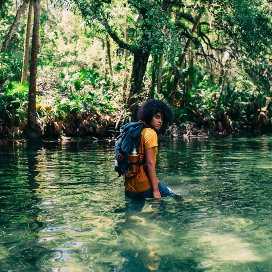 A backpacker walks through water in a lush green forest.