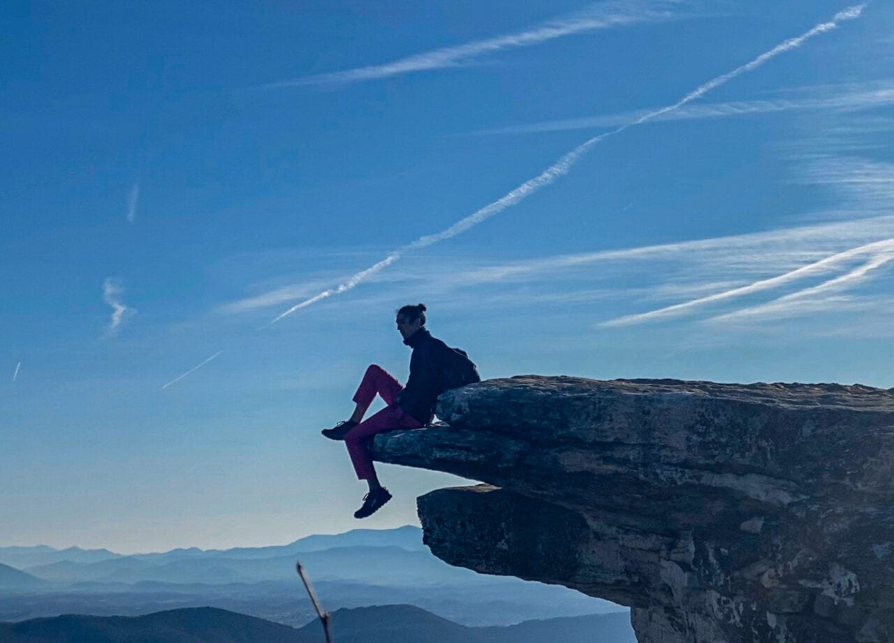 A man sitting on the edge of a rock cliff.