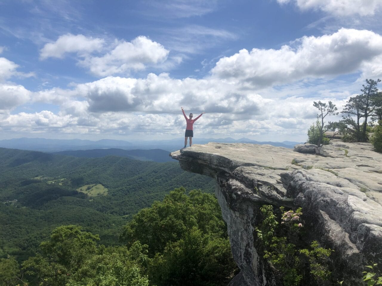 A woman standing on a cliff on the Appalachian Trail.