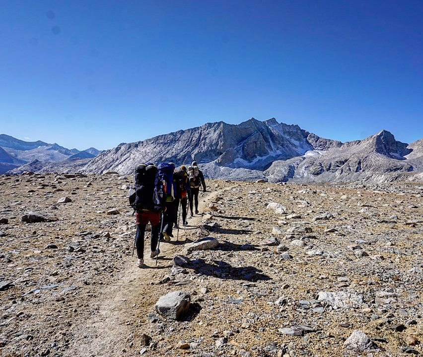 A group of hikers in a line on a trail.
