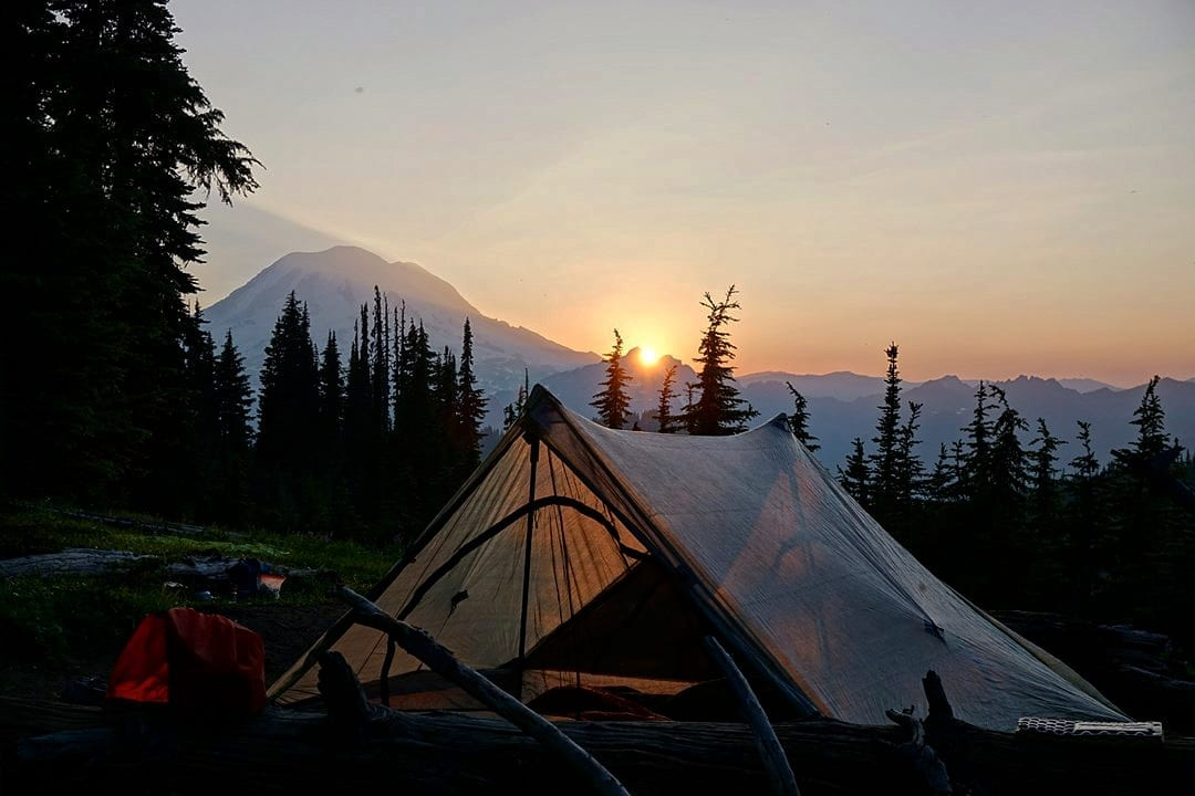 A tent with a sunset in the background.
