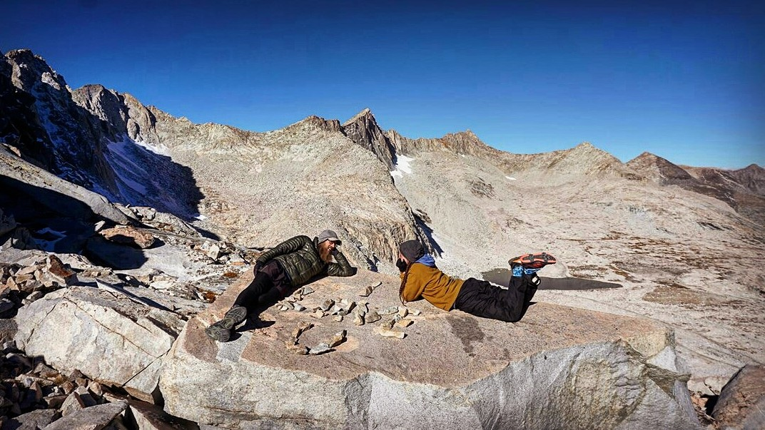 Hikers laying out on a rock.