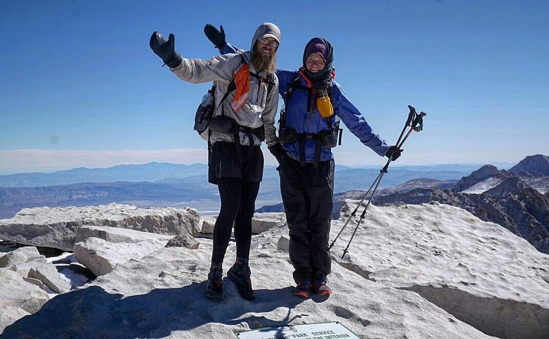 Two hikers standing on top of a mountain with their arms up.