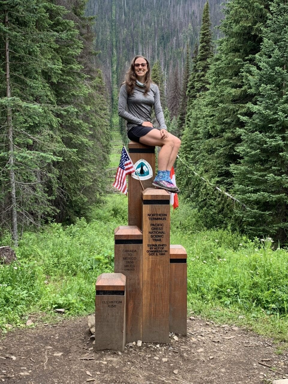 A woman sitting on top of the PCT northern terminus.