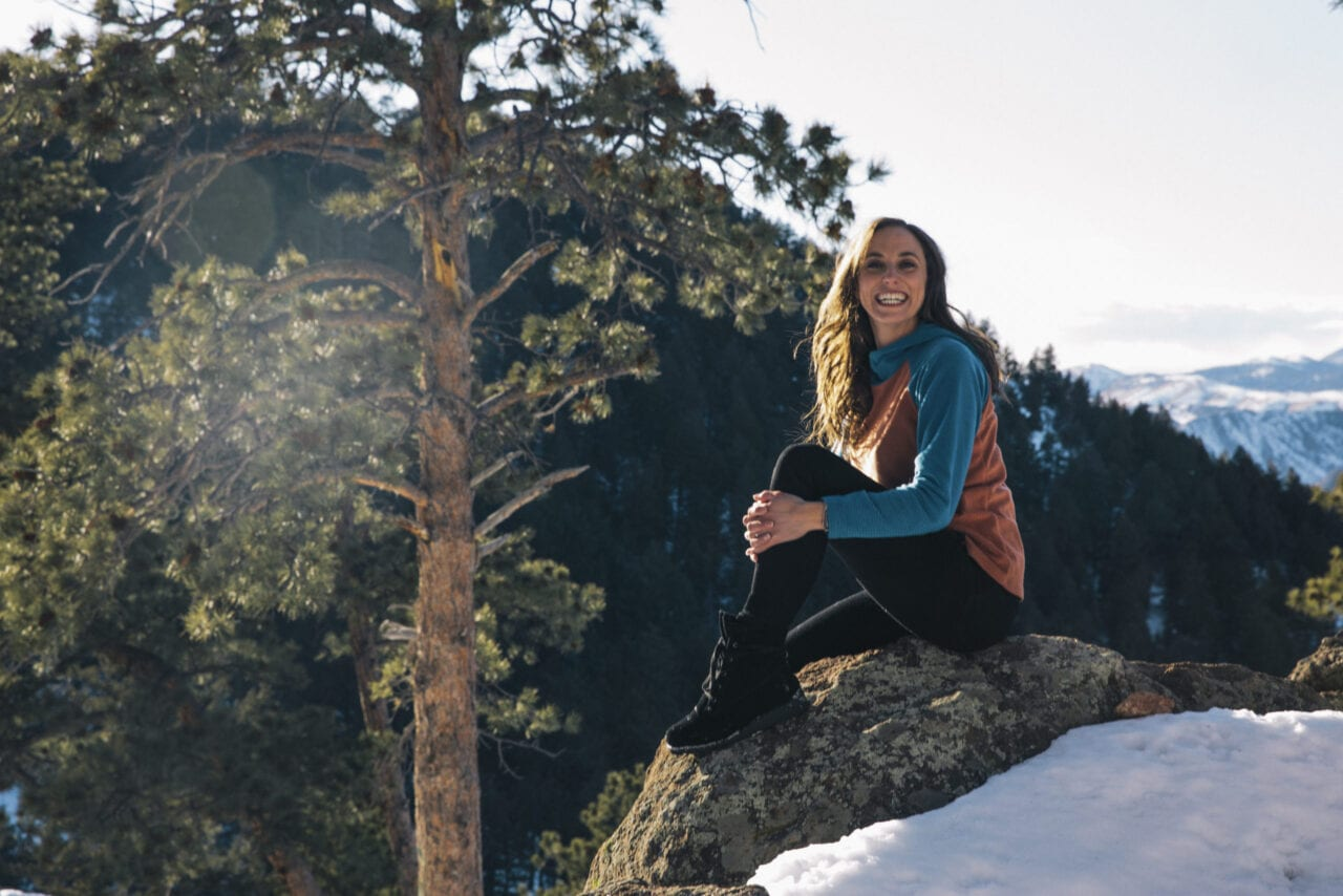 A woman sitting on a rock smiling.