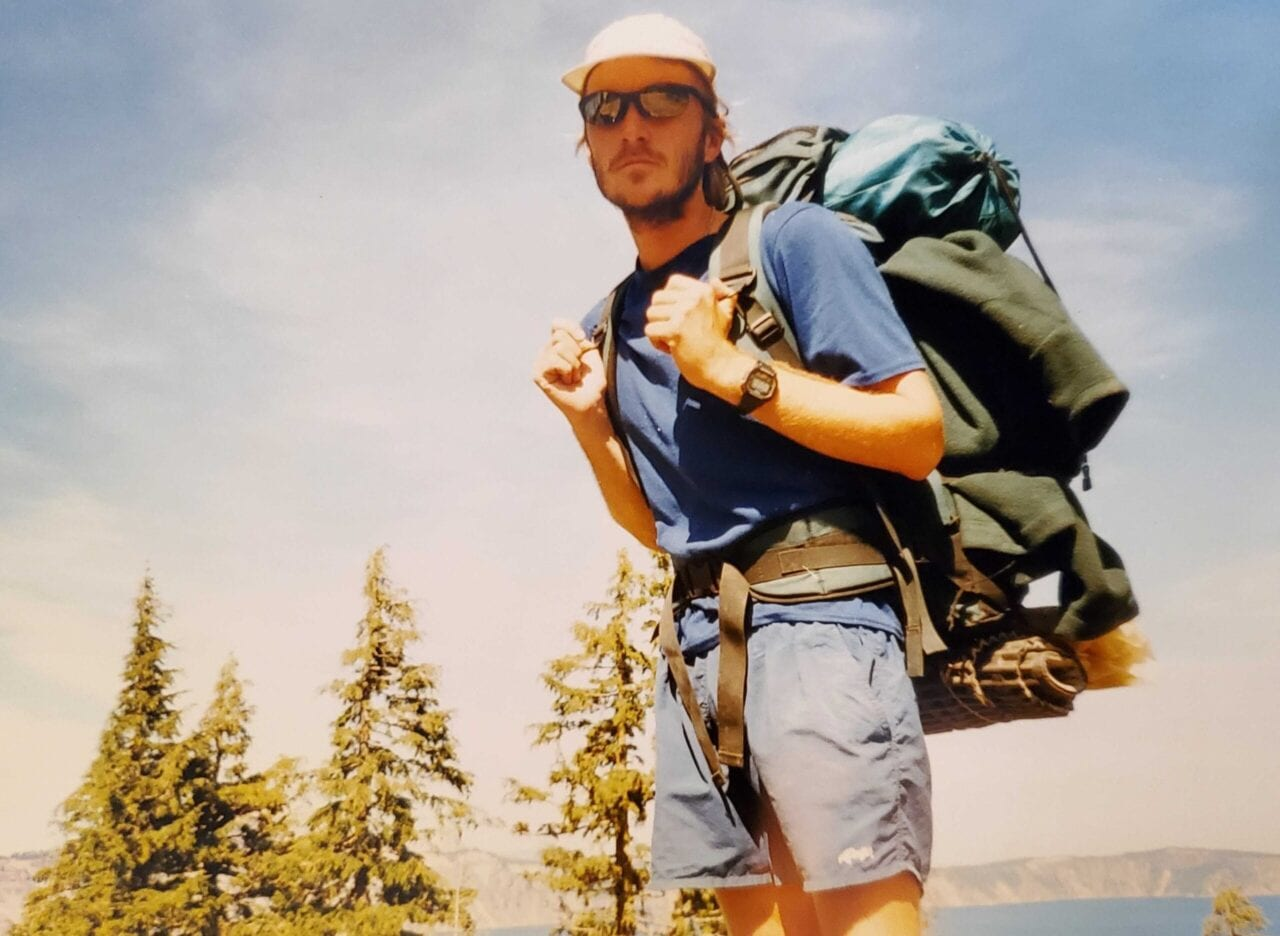 A man thru-hiking with his backpack on.