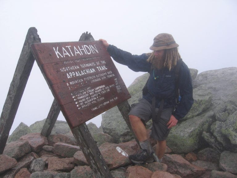 Guthook standing next to the sign on Mount Katahdin.