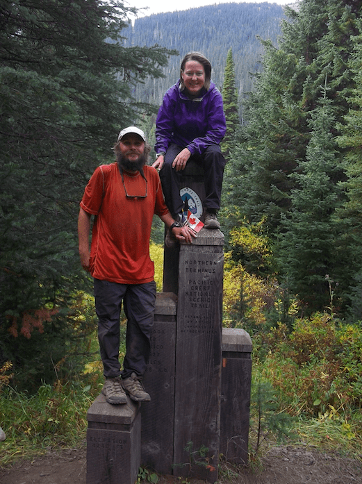 Two thru-hikers standing on the northern terminus of the PCT.