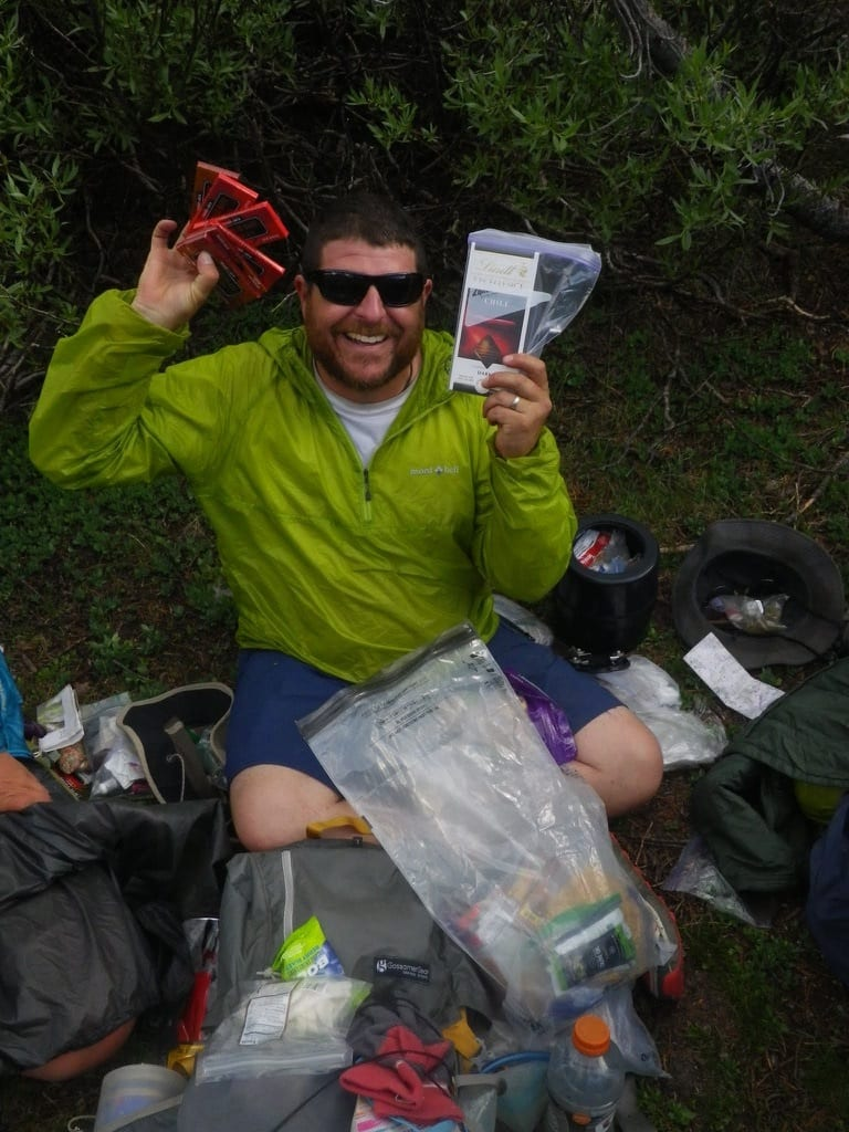 A hiker sitting on the ground surrounded by backpacking gear and food, while he holds up chocolate bars.