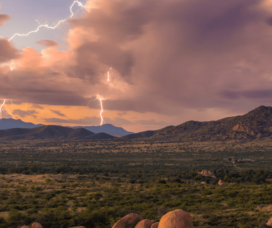 A lightning strike in the distance past some mountains and hills.