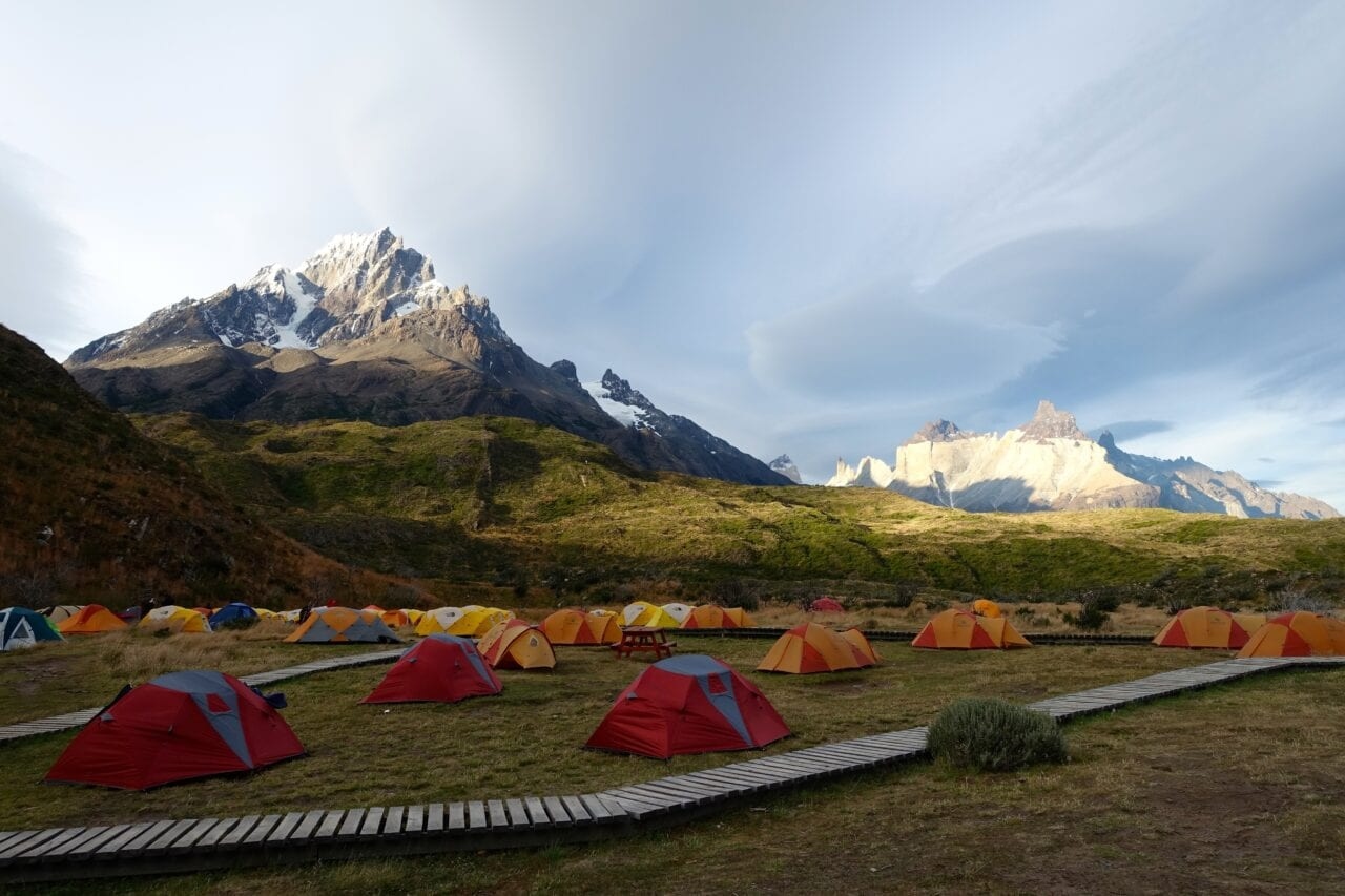 Several red and yellow tents set up in a campground with a mountain in the background.