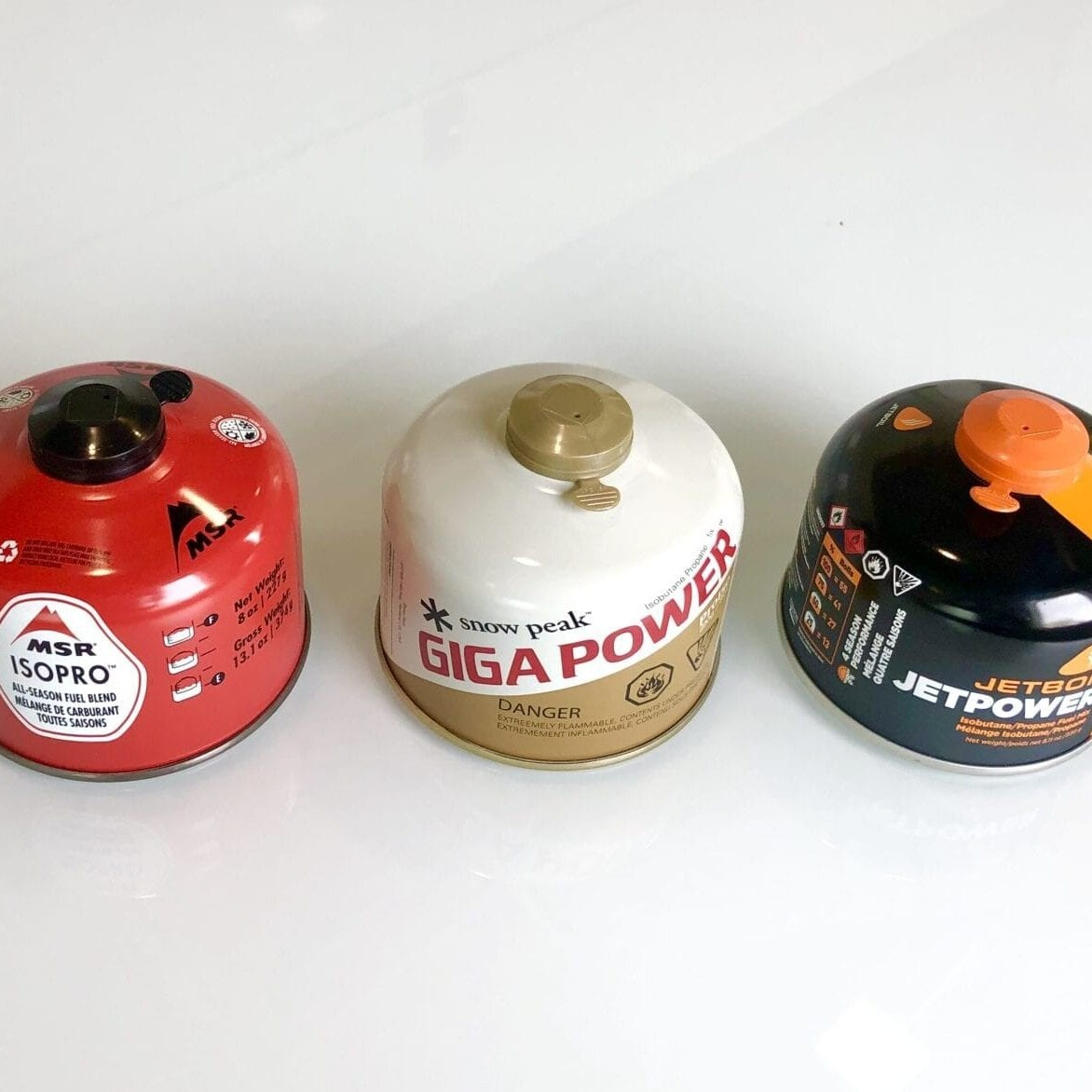 Three different brands of fuel canisters.
