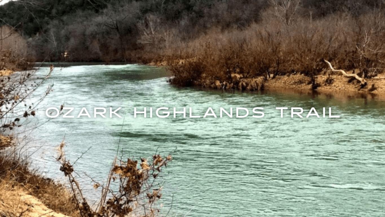 A blue river flows through a deciduous forest and sandy shores.