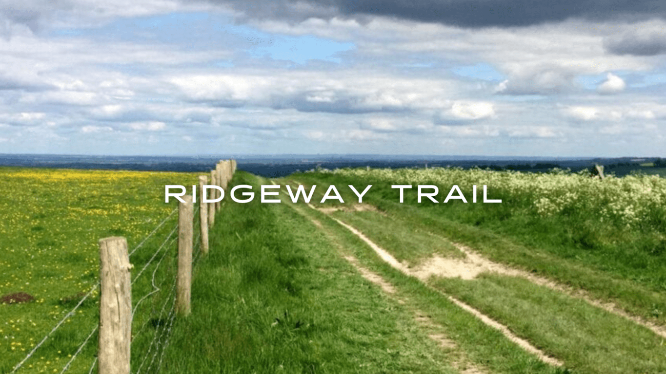 A trail and fence lead through a green field towards a distant horizon.