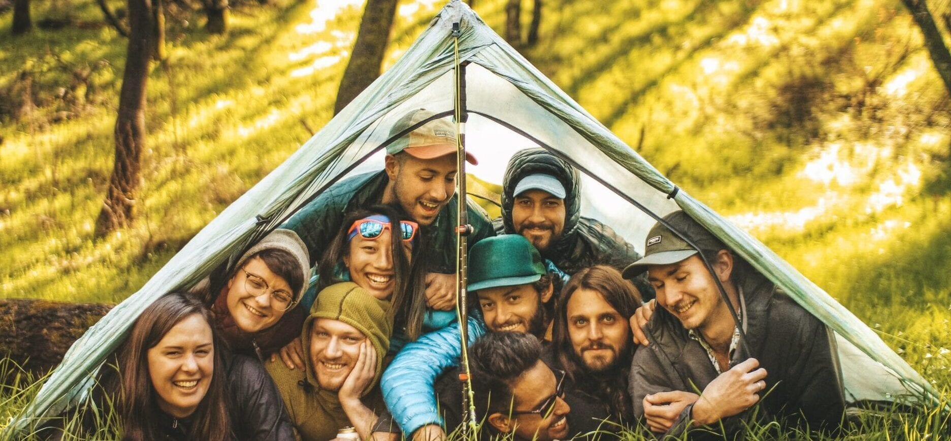 Ten laughing hikers cram into a small tent.