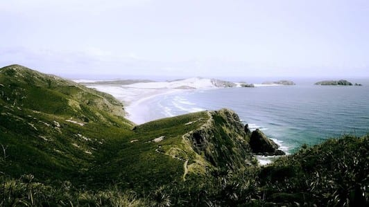 A view from Cape Reinga on the Te Araroa on the North Island of New Zealand looks over beautiful blue ocean, white sand beaches, and green hills.