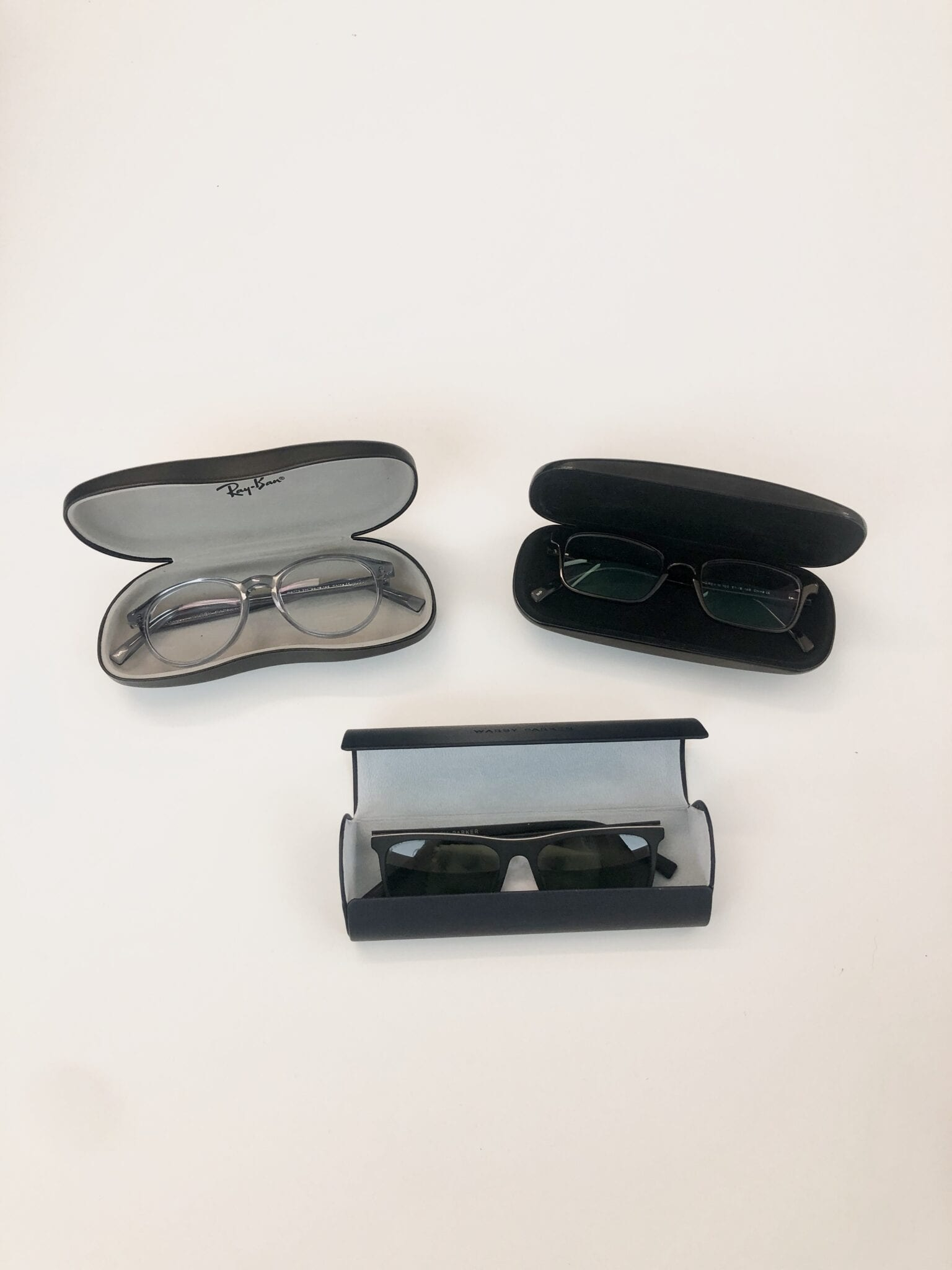 Three black glasses cases open with glasses in them on a table.