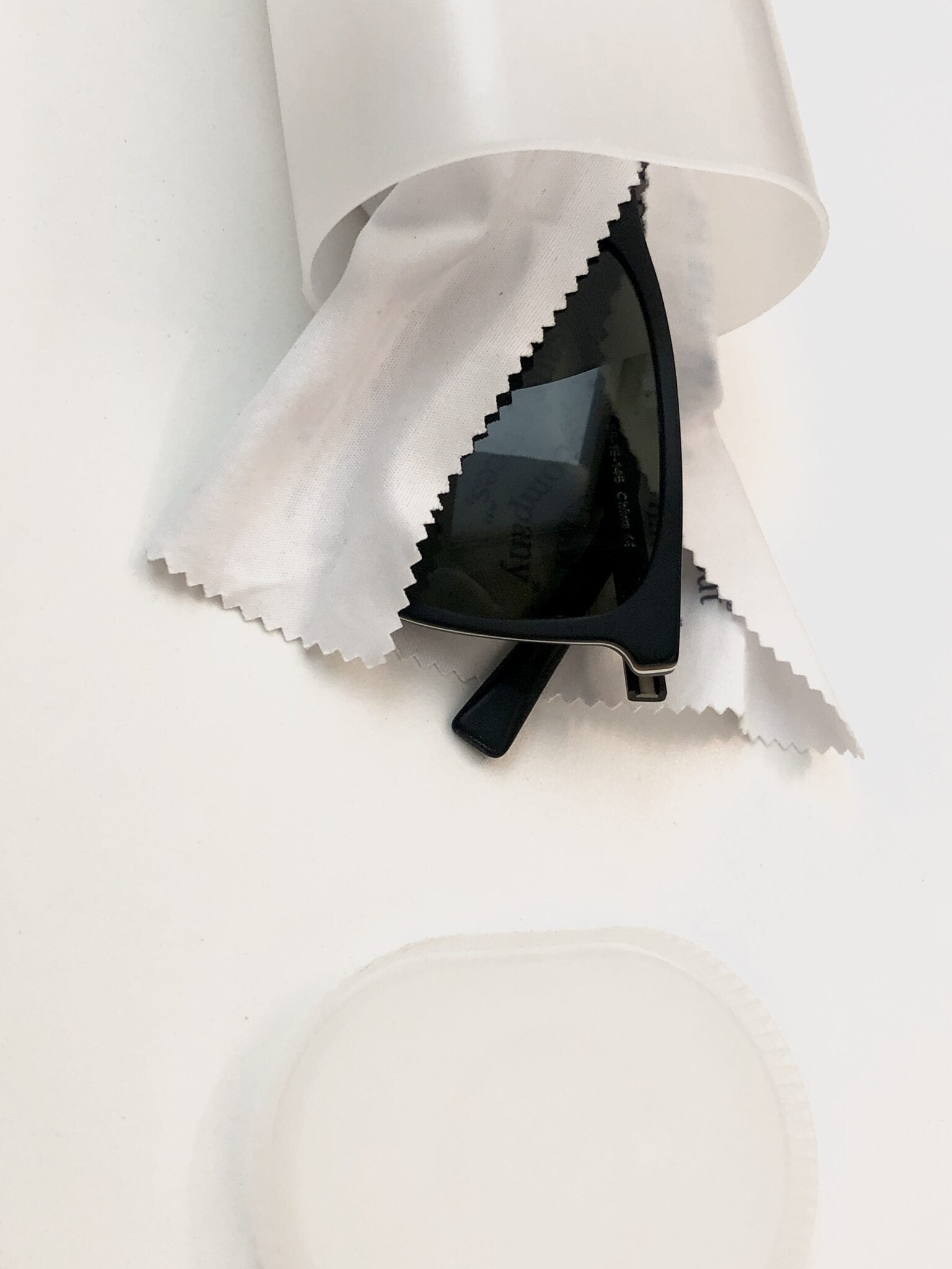 A pair of sunglasses wrapped in a cloth inside a Crystal Light container.