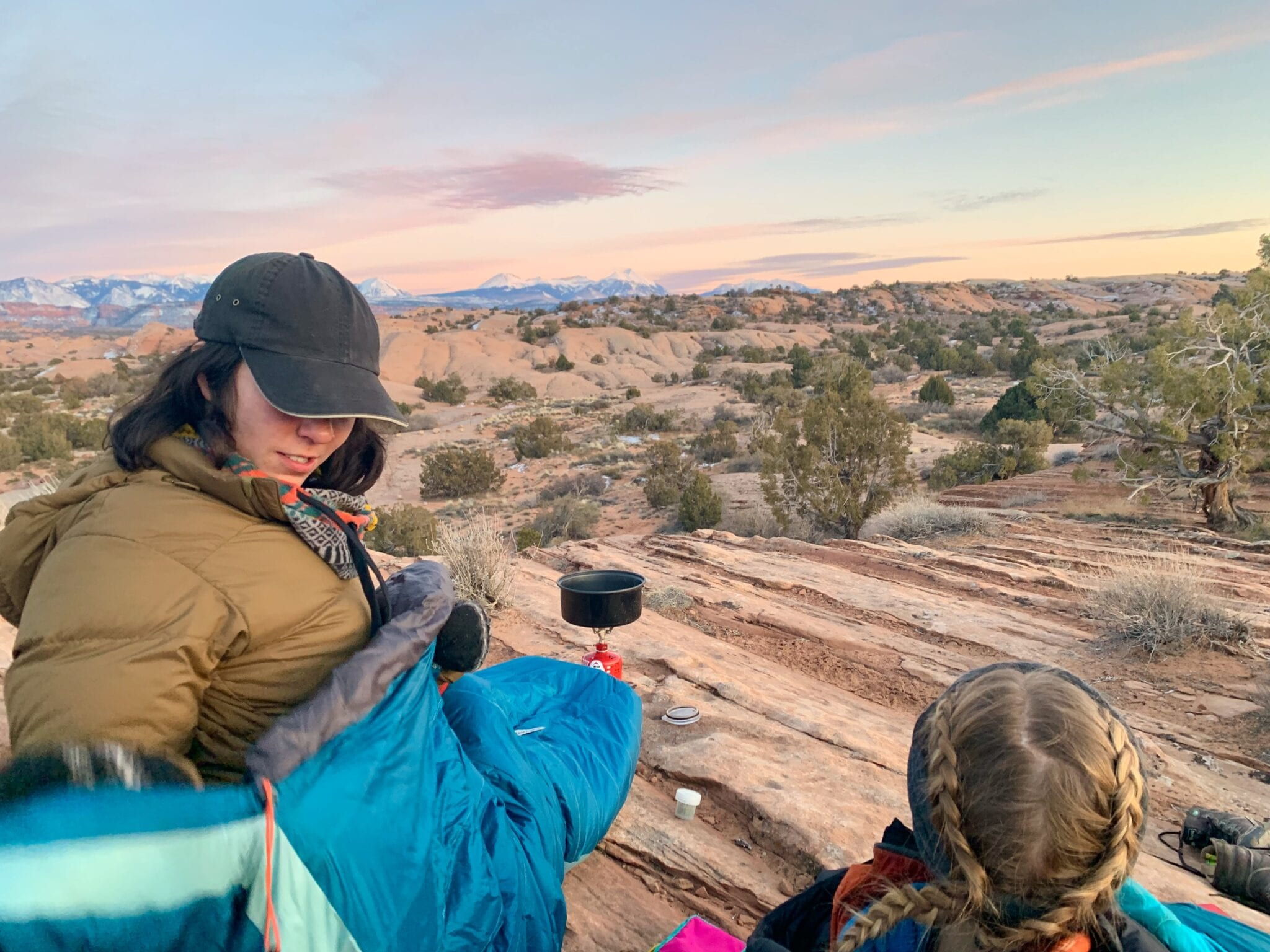 Two hikers make dinner on a stove at sunset