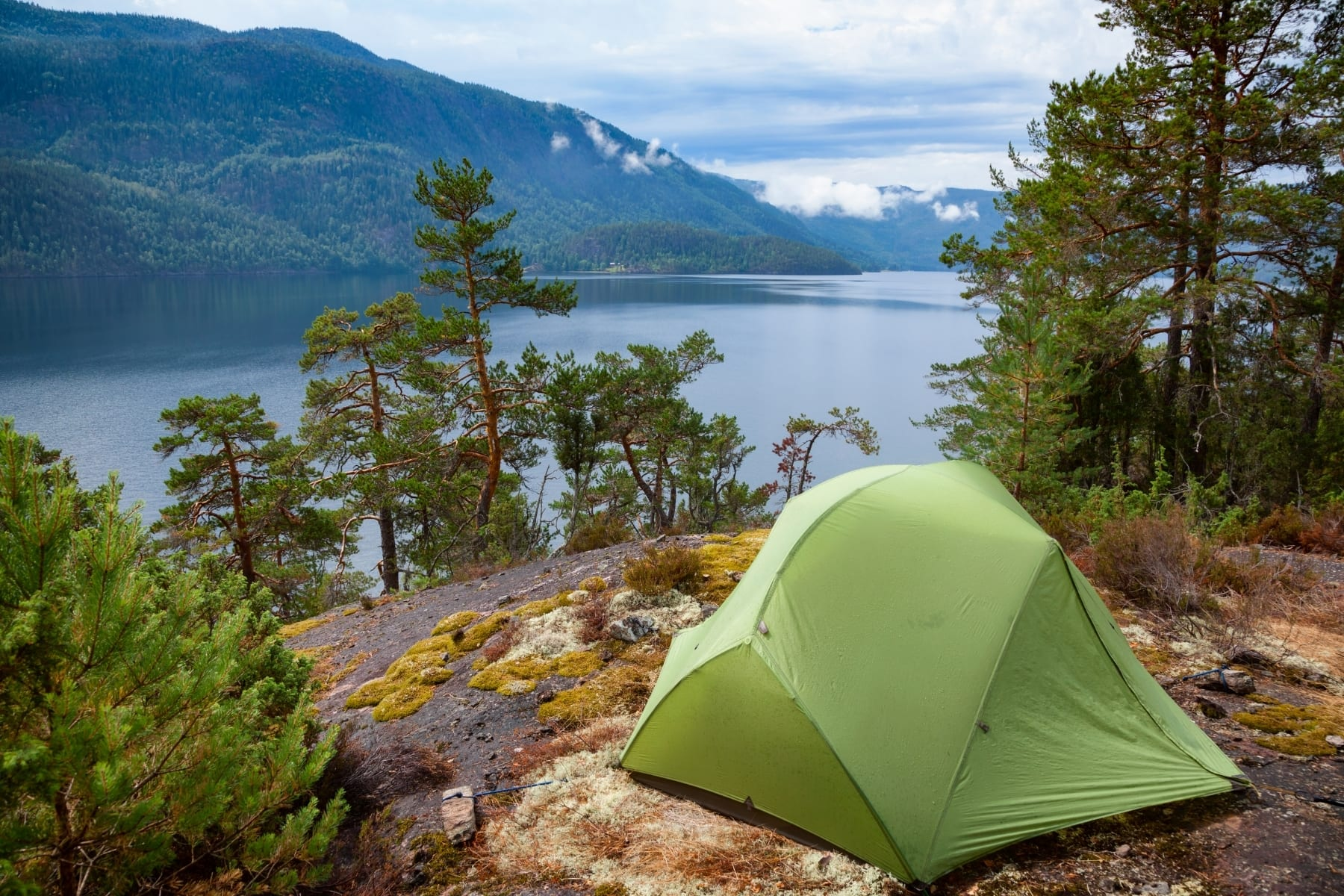 A green tent overlooking a lake and mountains
