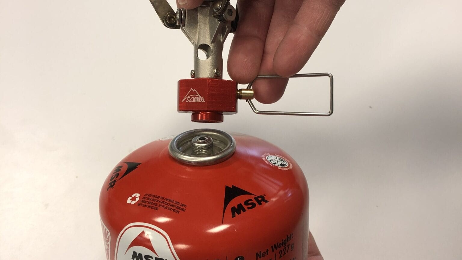 A backpacking stove being connected to a fuel canister.