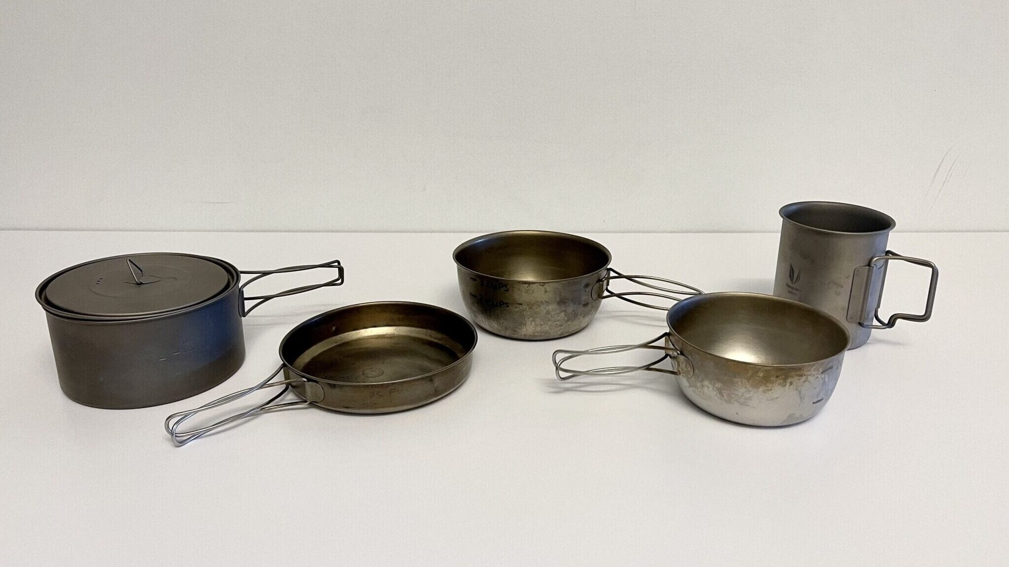 Five different sized backpacking cooking pots on a table.
