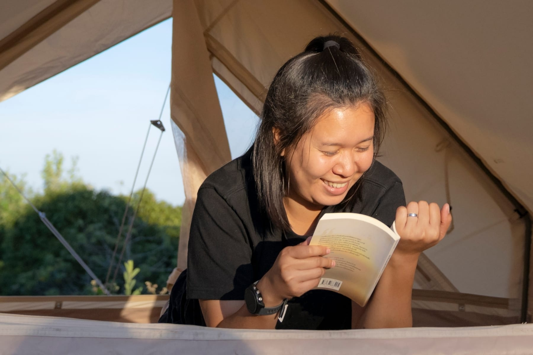 A woman reading a book in a tent.