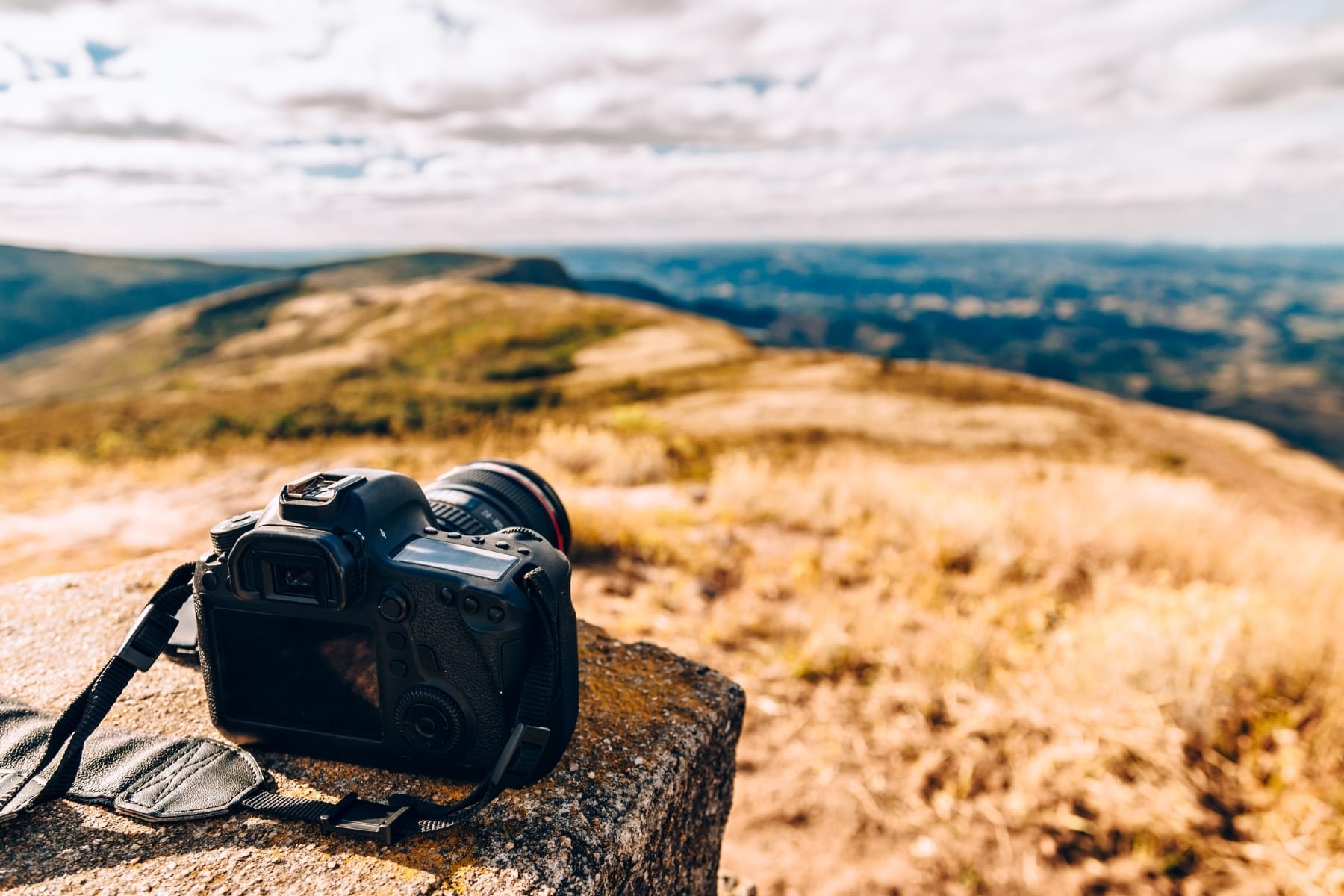 A DSLR camera on a rock outside.