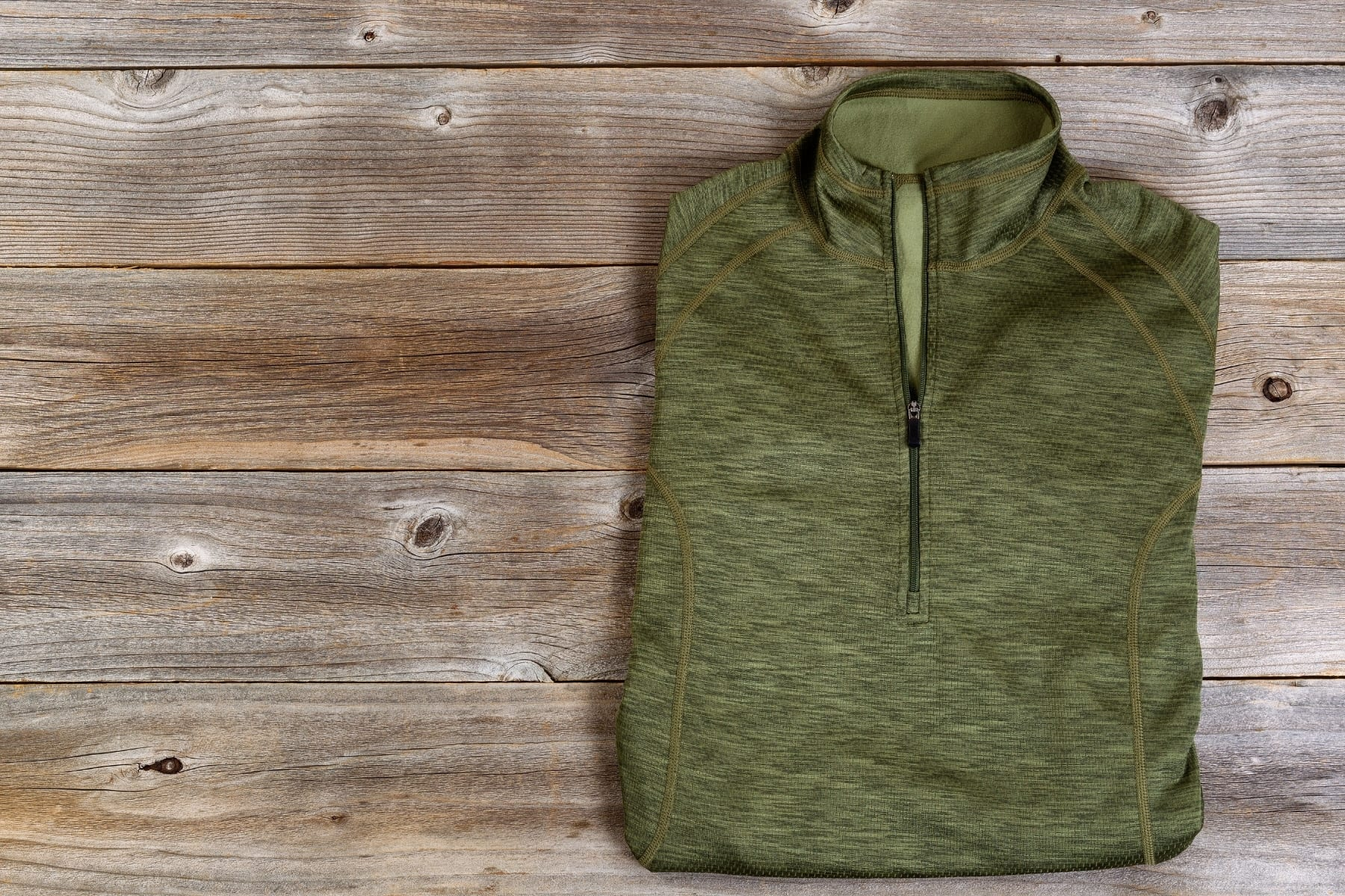 A green zip up jacket folded on a wooden background.