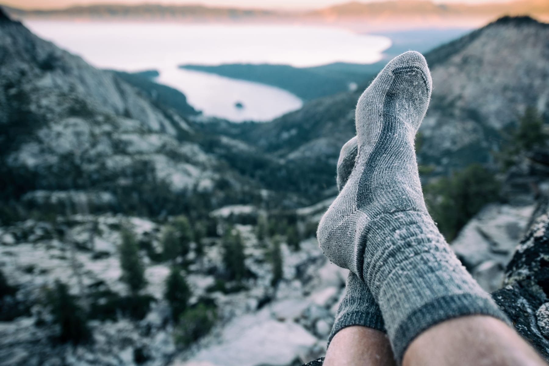 A person wearing socks with a view of mountains and a lake in the background.