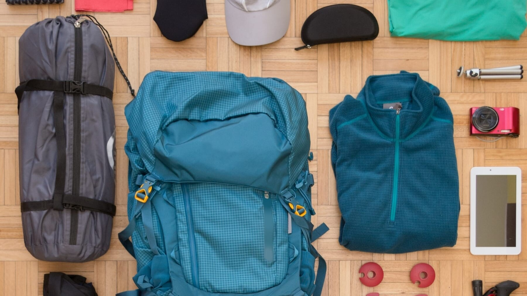 Backpacking gear laid out on the floor.