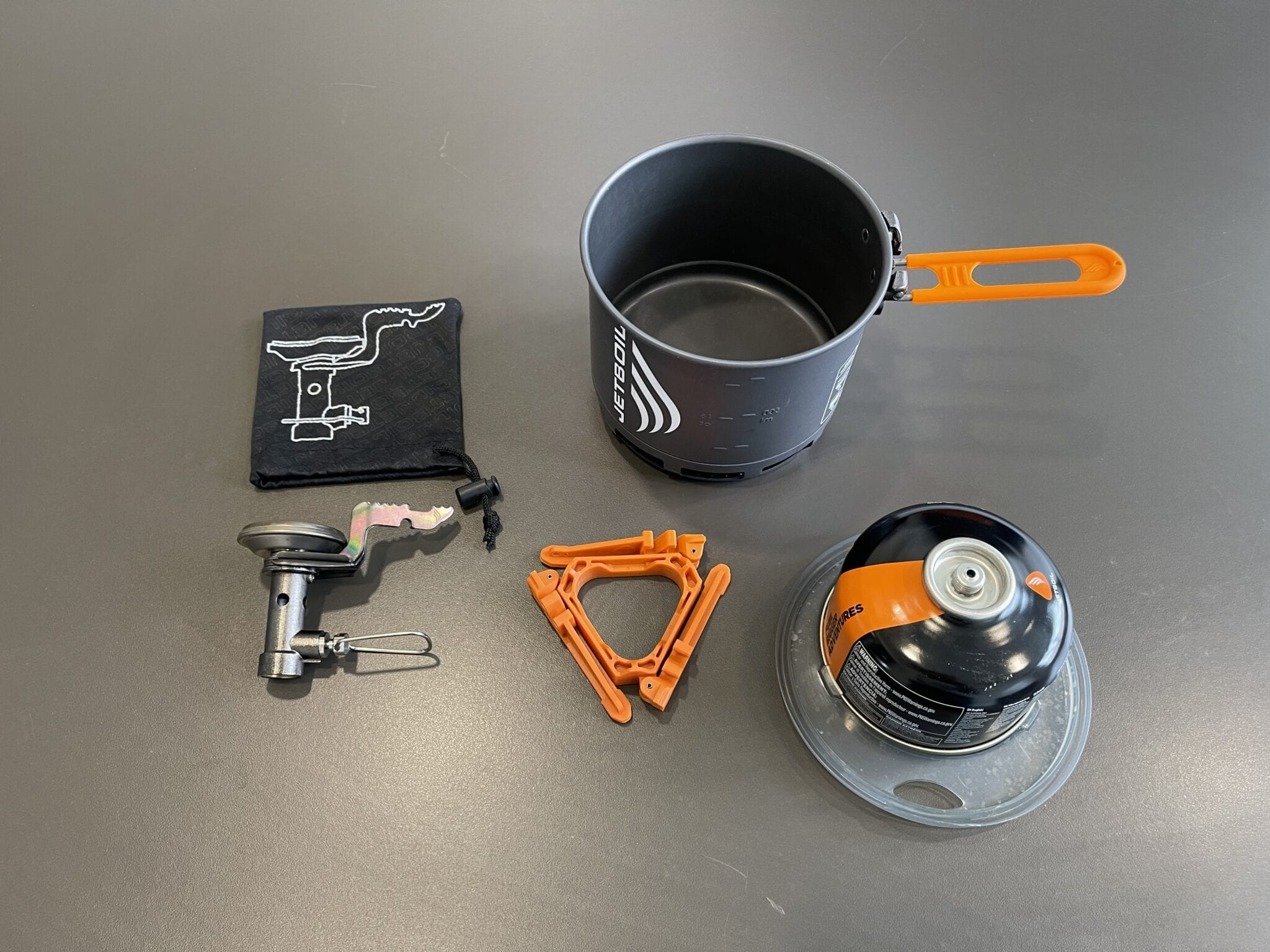 The Jetboil Stash stove system disassembled and laid out on a table.