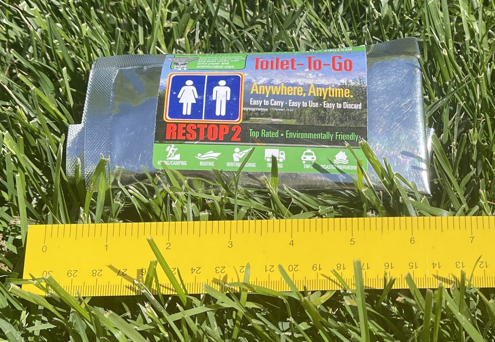 the toilet to go in grass with a ruler next to it measuring how long it is in length
