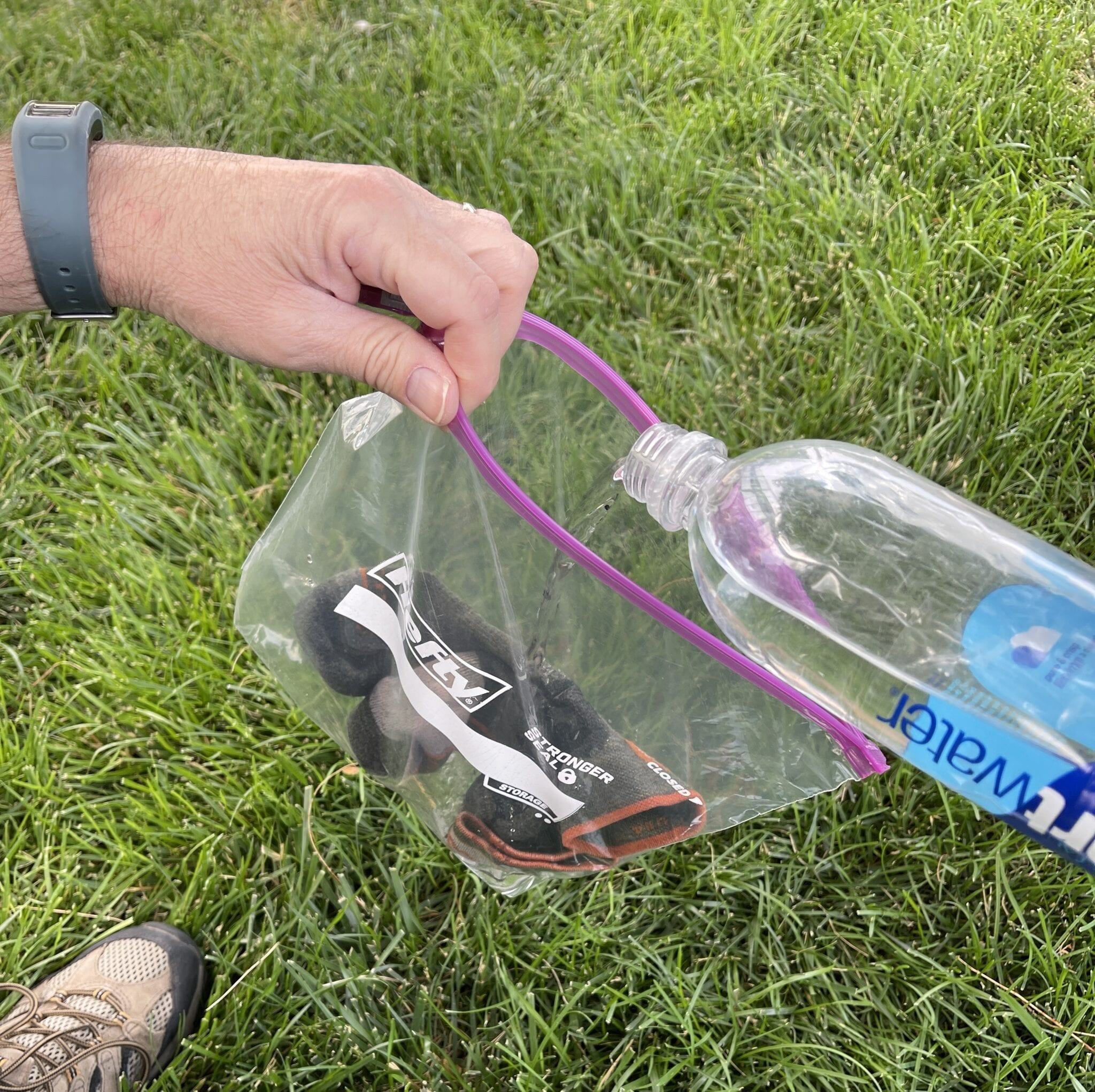 pouring water over dirty socks into ziploc bag