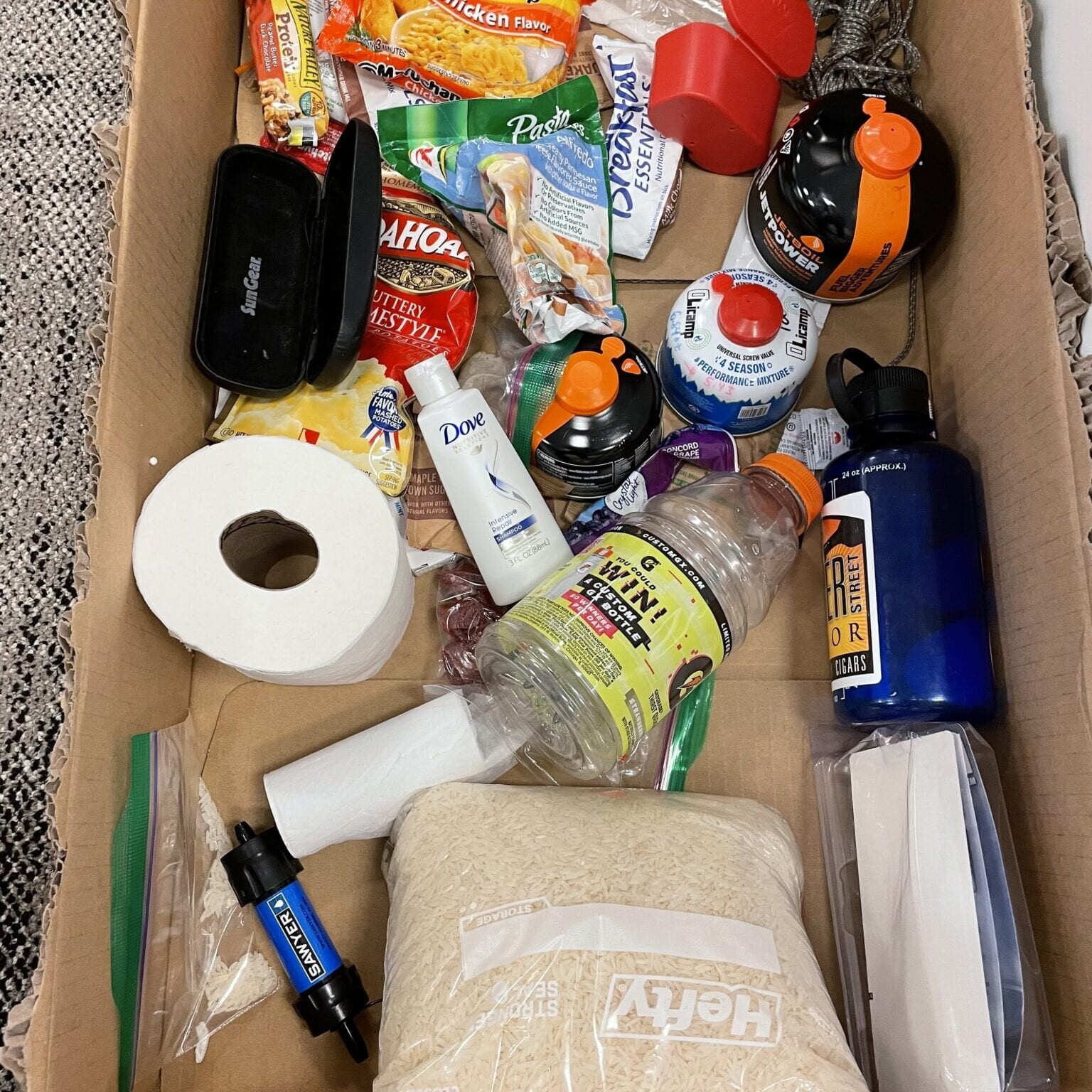 hiker box with random supplies like toilet paper, ramen, stoves, and a water filter