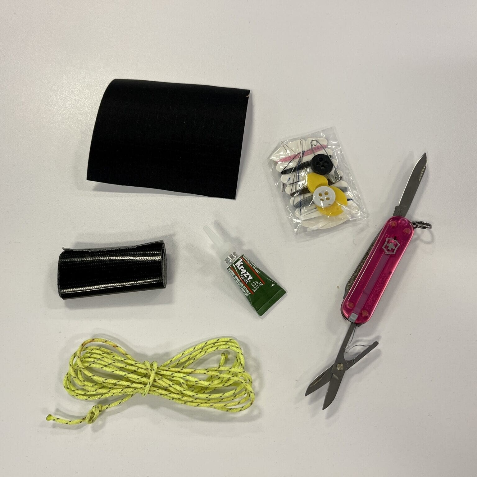 sewing kit, crazy glue, swiss army knife, rope, and tape laid across a table