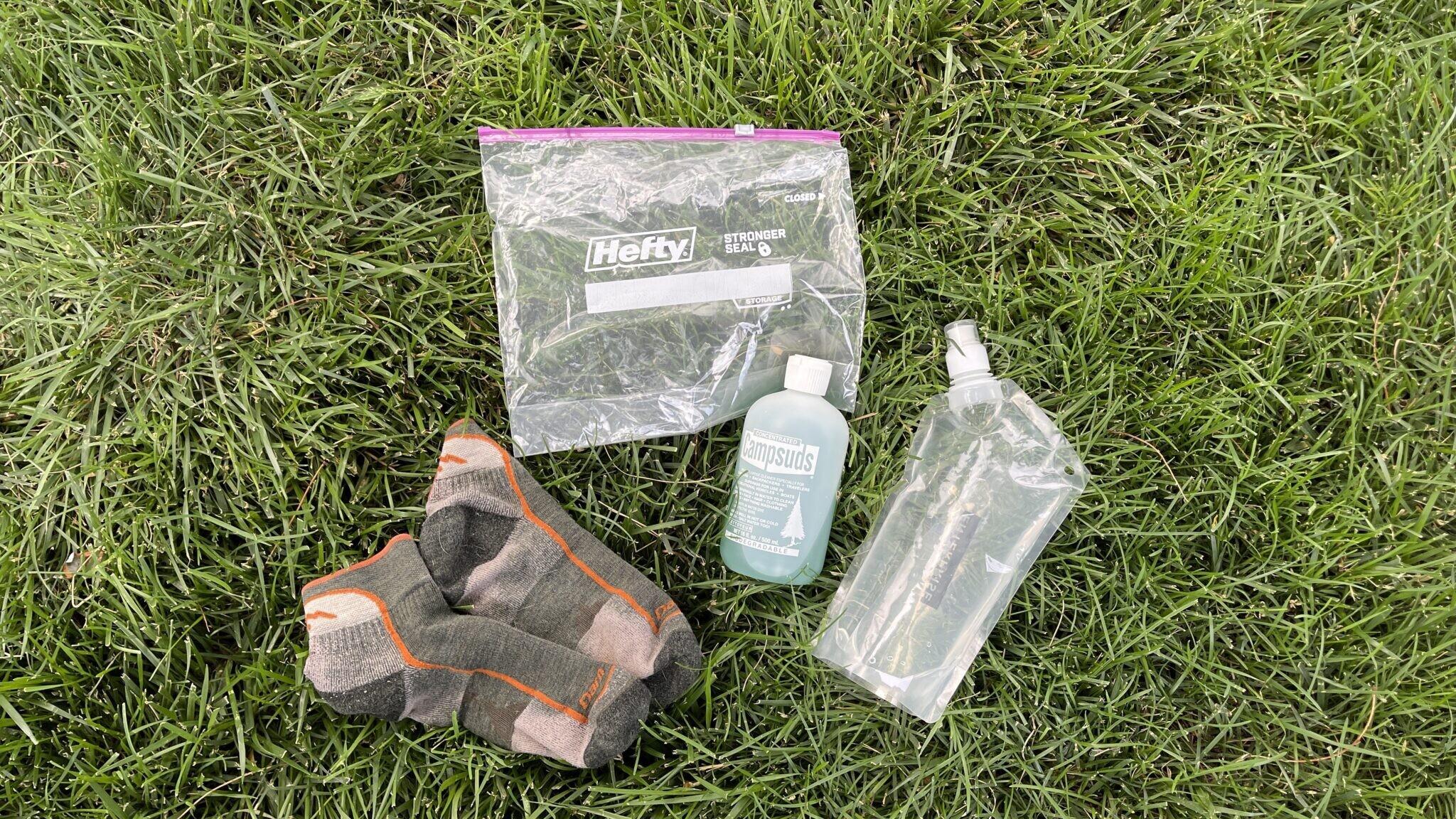 dirty socks, platypus water bottle, hiking detergent, plastic zipl oc bags assorted on grass