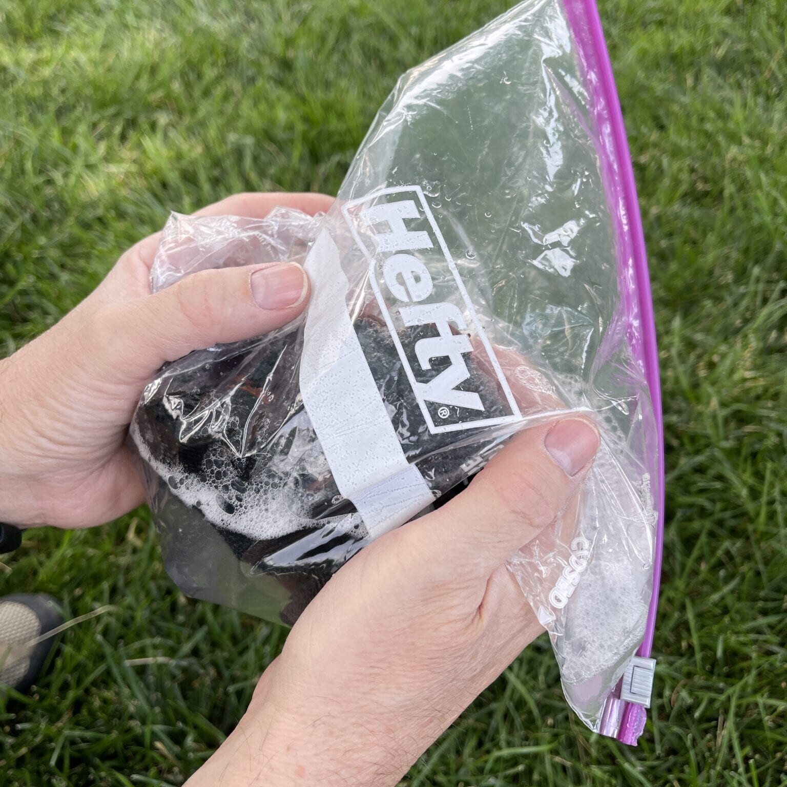soapy socks being immersed into ziploc bag with soapy water