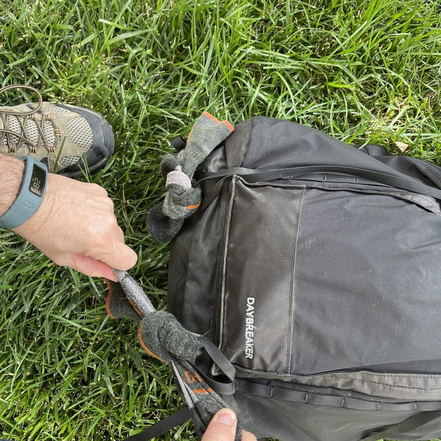 tying socks onto hiker backpack to dry