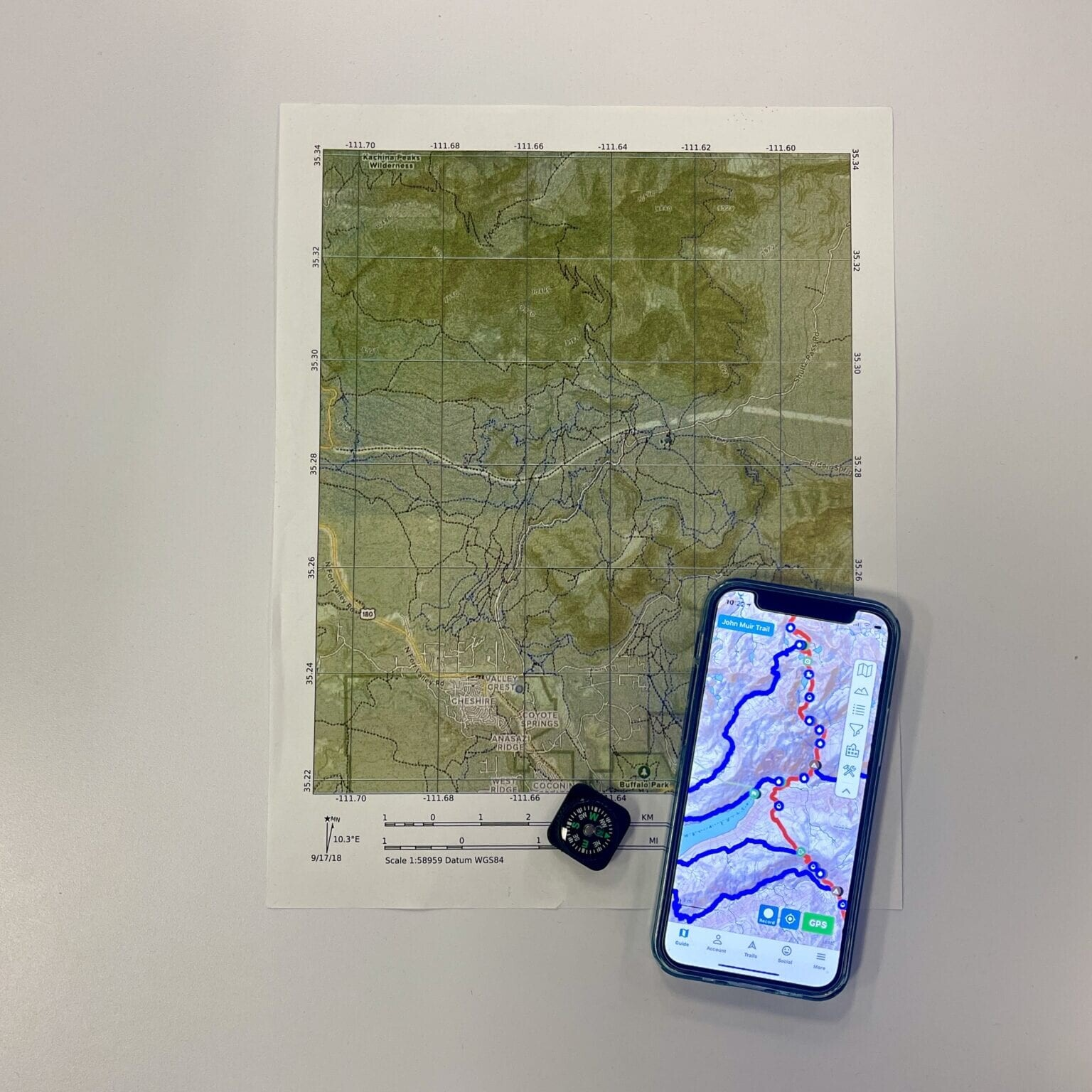 map of john muir trail on paper and in the guthook app with a compass lying next to it