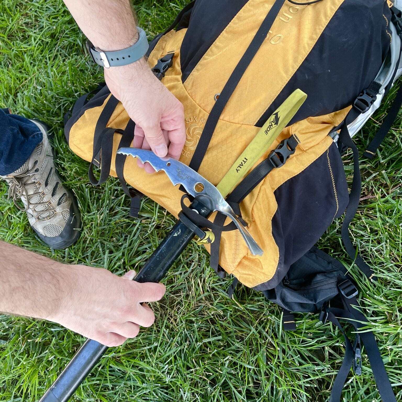 ice axe being attached to a backpack