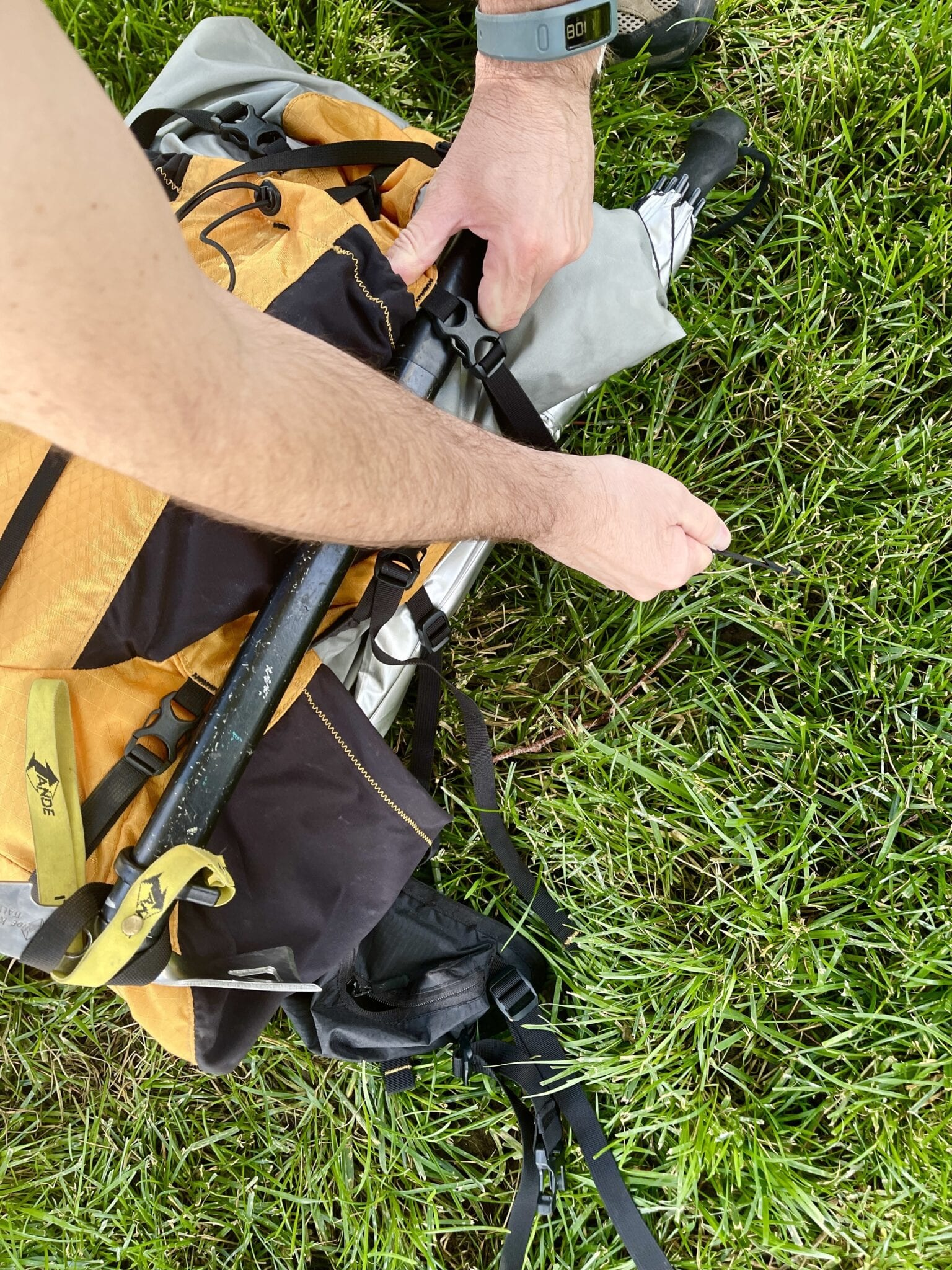 ice axe being fastened into backpack
